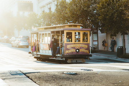 Historic Cable Car riding on famous California Street in beautiful golden evening light at sunset, San Francisco, California, USA