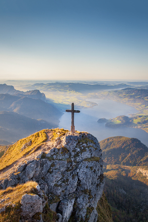 Panoramic view of an idyllic mountain scenery in the Alps with a wooden cross on a mountain summit in golden evening light at sunset. Stock Photo