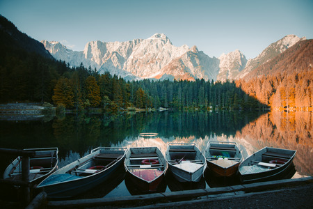 Beautiful morning view of famous Superior Fusine Lake with boats and Mount Mangart in the background at sunrise, Tarvisio, Udine province, Friuli Venezia Giulia, Italy Stock Photo