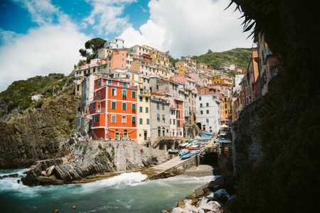 Classic view of beautiful Riomaggiore, one of the five famous picturesque fisherman villages of Cinque Terre, on a sunny day with blue sky and clouds in summer, Liguria, Italy