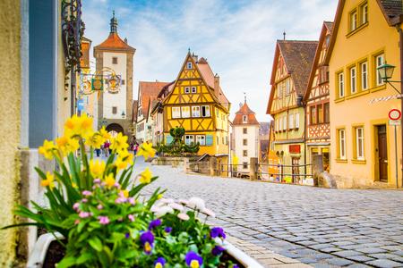 Klassieke weergave van de middeleeuwse stad Rothenburg ob der Tauber met bloeiende bloemen op een mooie zonnige dag met blauwe lucht en de wolken in de lente, Beieren, Duitsland Stockfoto