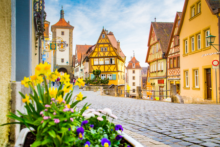 Klasyczny widok na średniowieczne miasto Rothenburg ob der Tauber z kwitnącymi kwiatami w piękny słoneczny dzień z błękitnym niebem i chmurami na wiosnę, Bawaria, Niemcy Zdjęcie Seryjne