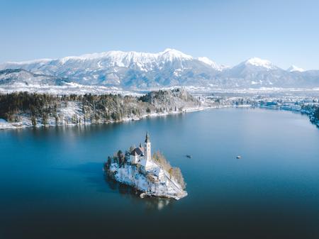 Panoramablick auf den malerischen Bleder See mit der berühmten Insel Bled und dem Schloss (Blejski grad) im Hintergrund an einem schönen sonnigen Tag im Winter, Slowenien