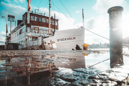 Beautiful view of old ship in Stockholm harbor reflecting in puddle in scenic evening light at sunset, Sweden, Scandinavia
