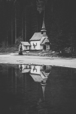 Beautiful vertical view of traditional little chapel at famous Lago di Braies reflecting in water, South Tyrol, Italy Stock Photo