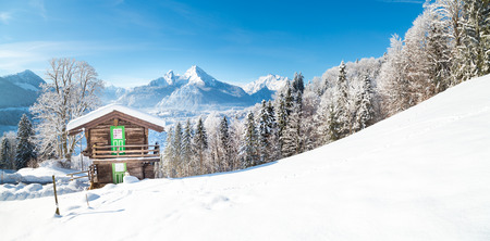 Panoramic view of traditional wooden mountain cabin in scenic winter wonderland mountain scenery in the Alps