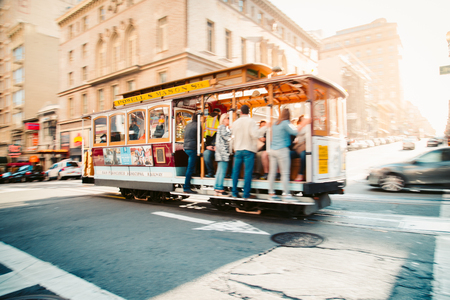 Traditional Powell-Hyde cable car riding in central San Francisco in beautiful golden evening light at sunset, California, USA