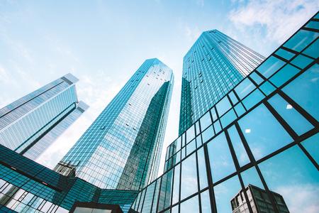 Vista de gran angular baja mirando hacia los modernos rascacielos en el distrito de negocios en un hermoso día soleado con cielo azul y nubes