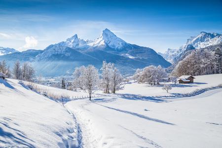 Schöne Winterlandschaft mit Bäumen und Berggipfeln in den Alpen an einem sonnigen Tag mit blauem Himmel und Wolken