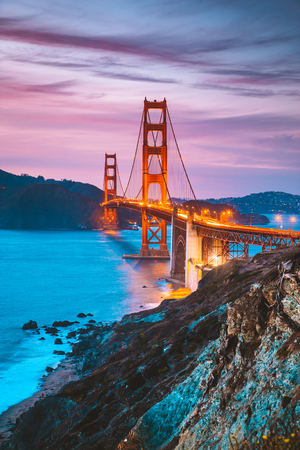 Classic panorama view of famous Golden Gate Bridge seen from scenic Baker Beach in beautiful post sunset twilight with blue sky and clouds at dusk in summer, San Francisco, California, USA 免版税图像 - 121796100