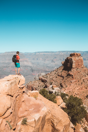 A young male hiker is standing on a rock enjoying the amazing view over famous Grand Canyon with the Colorado river flowing on a beautiful sunny day in summer, Arizona, USA Фото со стока