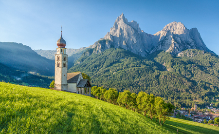 Panoramic view of idyllic mountain scenery in the Dolomites with St. Valentin Church and famous Mount Sciliar in beautiful morning light at sunrise, village of Seis am Schlern, South Tyrol, Italy