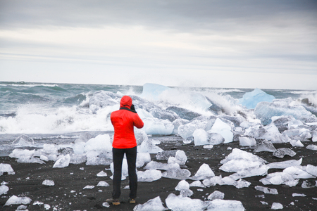 Hiker watching waves crash against icebergs at famous Diamond Beach, Jokulsarlon glacier lagoon, Vatnajokull National Park, Iceland