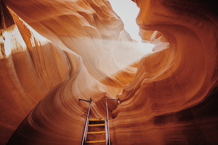 Schöne Ansicht von erstaunlichen Sandsteinformationen mit einer Leiter, die in Richtung zu einen magischen Lichtstrahl in der berühmten Antilopen-Schlucht nahe der historischen Stadt der Seite am See Powell, amerikanischer Südwesten, Arizona, USA führt Standard-Bild
