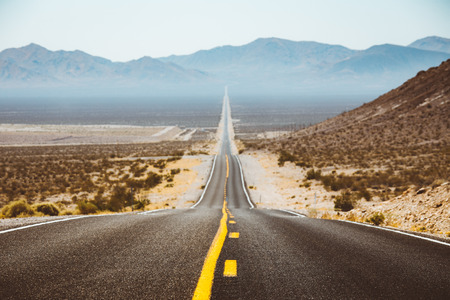 Classic panorama view of an endless straight road running through the barren scenery of the American Southwest with extreme heat haze on a beautiful sunny day with blue sky in summer Imagens