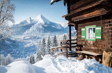 Schöne Aussicht auf die traditionelle Holzberghütte in der malerischen Winterlandschaft der Alpen in den Alpen Standard-Bild