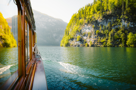 Traditional passenger boat gliding on Lake Konigssee with Watzmann mountain in the background on a beautiful sunny day in summer, Berchtesgadener Land, Bavaria, Germany