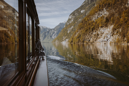 Classic view of traditional passenger boat on famous Lake Konigssee on a beautiful sunny day with blue sky and clouds in fall, Berchtesgadener Land, Bavaria, Germany