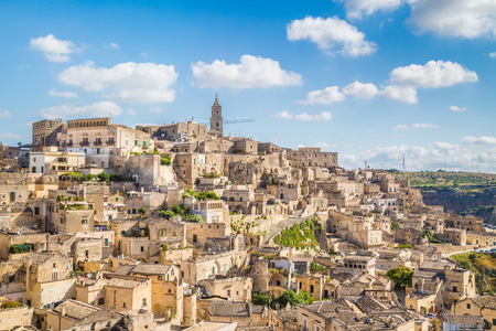 Panoramic view of the ancient town of Matera (Sassi di Matera) on a sunny day with blue sky and clouds, Basilicata, southern Italy