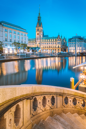 Classic twilight view of Hamburg city center with historic town hall reflecting in Binnenalster during blue hour at dusk, Germany