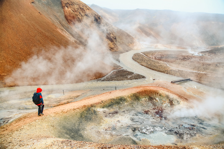 Beautiful view of idyllic geothermal mountain scenery with person hiking in Landmannalaugar in the highlands of Iceland