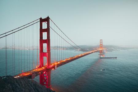 Klasyczny panoramiczny widok na słynną Golden Gate ze statkiem towarowym w pięknym zmierzchu po zachodzie słońca podczas niebieskiej godziny o zmierzchu latem, San Francisco, Kalifornia, USA Zdjęcie Seryjne