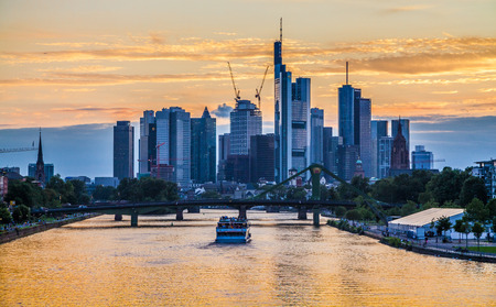 Classic panoramic view of famous Frankfurt am Main skyline with dramatic clouds and passenger ship in beautiful golden post sunset twilight during blue hour at dusk, Hessen, Germany