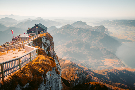 Beautiful mountain scenery in the Alps with alpine mountain hut on Schafberg summit in golden evening light at sunset
