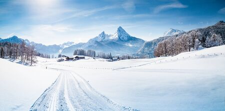 Scenic winter wonderland mountain scenery in the Alps with cross-country skiing track on a cold sunny day with blue sky and clouds Stock Photo
