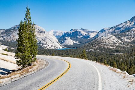 Empty road running through Sierra Nevada mountain scenery with on sunny day in summer, Yosemite National Park, California, USA