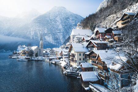 Vue de carte postale classique de la célèbre ville au bord du lac de Hallstatt dans les Alpes avec un navire à passagers par une belle journée froide et ensoleillée avec ciel bleu et nuages en hiver, région du Salzkammergut, Autriche