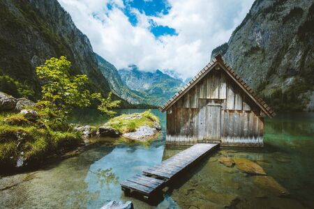 Panoramic view traditional old wooden boat house at scenic Lake Obersee on a beautiful day with blue sky and clouds in summer, Bavaria, Germany
