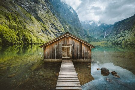 Panoramic view of traditional old wooden boat house at scenic Lake Obersee on a beautiful day with blue sky and clouds in summer, Bavaria, Germany