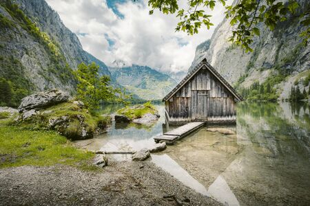 Idyllic view of traditional old wooden boat house at scenic Lake Obersee on a beautiful sunny day with blue sky and clouds in summer, Nationalpark Berchtesgadener Land, Bavaria, Germany 写真素材
