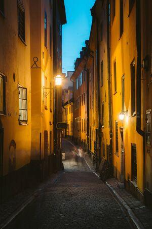 Vista clásica del crepúsculo de casas tradicionales en un hermoso callejón en el histórico Gamla Stan (Old Town) de Estocolmo iluminado durante la hora azul al atardecer, el centro de Estocolmo, Suecia