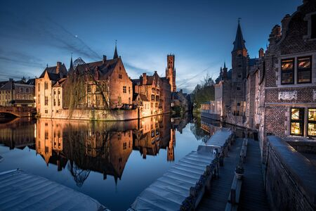 Classic postcard view of the historic city center of Brugge, often referred to as The Venice of the North, with famous Rozenhoedkaai illuminated in beautiful twilight, West Flanders province, Belgium 写真素材