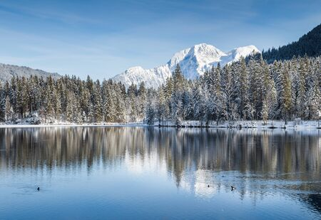 Idyllic winter wonderland with crystal clear mountain lake in the Alps on a beautiful cold sunny day