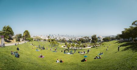 Panorama view of people in San Francisco's Mission Dolores Park enjoying the sunny weather on a beautiful day with clear blue skies with the skyline in the background, San Francisco, California, USA Archivio Fotografico - 138055102