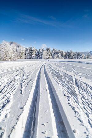 Nahaufnahme einer leeren Langlaufloipe in einer wunderschönen Winterlandschaft