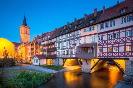 Classic panoramic view of the historic city center of Erfurt with famous Krämerbrücke bridge illuminated at beautiful twilight during blue hour, Thüringen, Germany Stock Photo