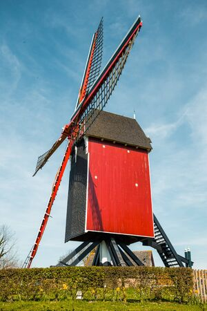 Beautiful view of traditional red wooden windmill against a blue sky with clouds in summer Standard-Bild