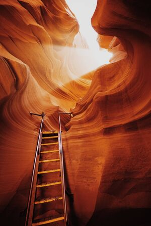 Beautiful view of amazing sandstone formations with a ladder leading toward a magic light beam in famous Antelope Canyon near the historic town of Page at Lake Powell, American Southwest, Arizona, USA 免版税图像