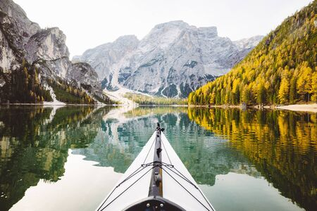 Beautiful view of kayak on a calm lake with amazing reflections of mountain peaks and trees with yellow autumn foliage in fall, Lago di Braies, Italy 免版税图像
