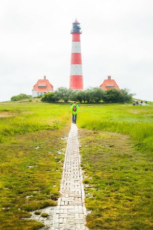 Man walking towards famous Westerheversand on a sunny day with blue sky and clouds in summer, North Sea, Schleswig-Holstein, Germany 版權商用圖片