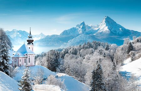 Beautiful winter wonderland mountain scenery in the Alps with pilgrimage church of Maria Gern and famous Watzmann summit in the background, Berchtesgadener Land, Bavaria, Germany