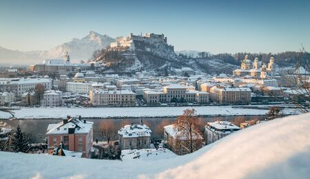 Classic view of the historic city of Salzburg with famous Hohensalzburg Fortress and Salzach river in scenic morning light at sunrise on a beautiful cold sunny day in winter, Salzburger Land, Austria Фото со стока