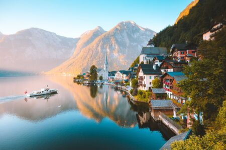 Classic postcard view of famous Hallstatt lakeside town in the Alps with traditional passenger ship in early morning light at dawn on a beautiful sunny day in summer, Salzkammergut region, Austria
