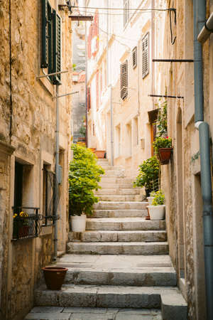 Scenic vertical view of small alleyway in an old town in Europe with golden light in summer