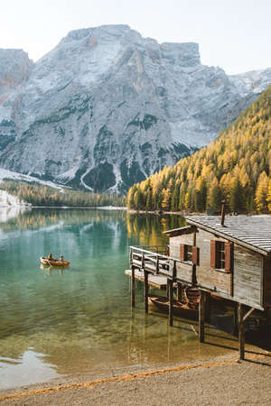 Scenic view of traditional wooden boathouse at famous Lago di Braies with Dolomited mountain peaks reflecting in lake, South Tyrol, Italy