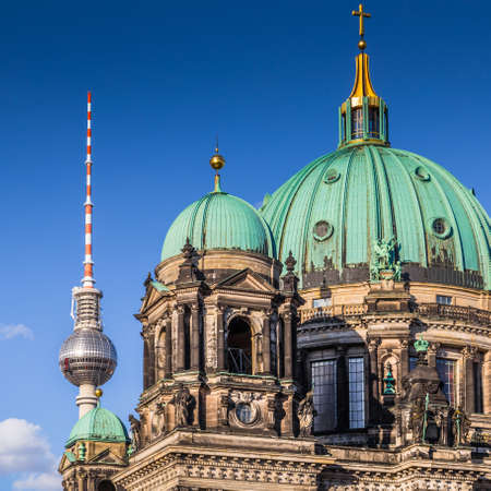 Closeup panorama view of historic Berlin Cathedral with famous TV tower in the background on a beautiful sunny day with blue sky and clouds in summer, central Berlin Mitte, Germany